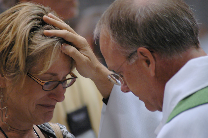 Bishop Michael Burke makes the sign of the cross in chrism oil on a worshipers forehead  in remembrance of her Baptism.