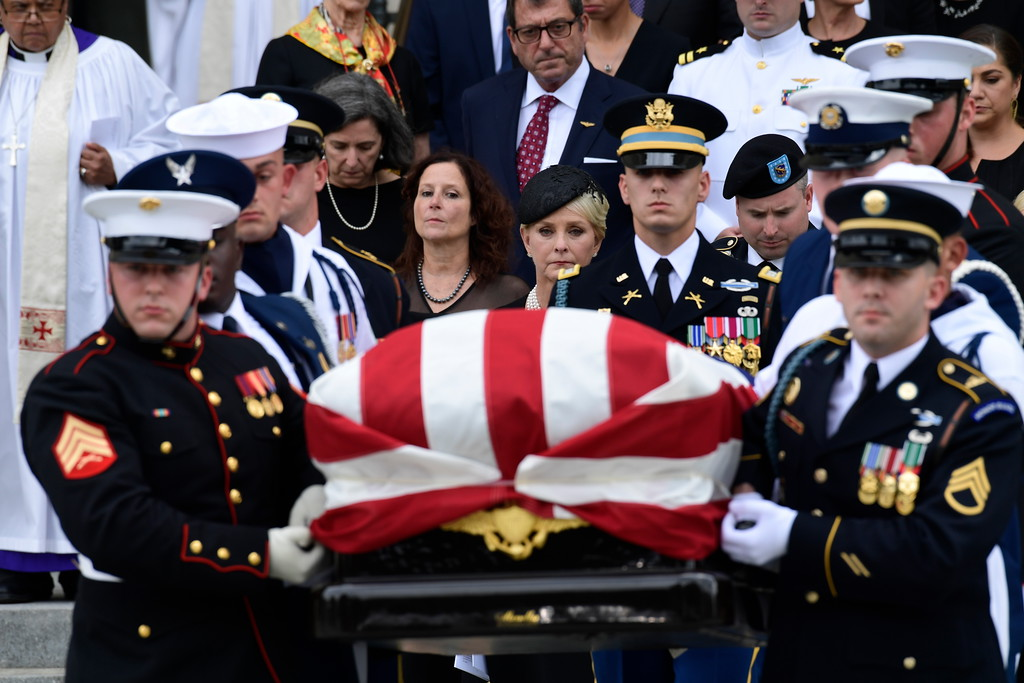. The casket of Sen. John McCain, R-Ariz., is carried out of the Washington National Cathedral in Washington, Saturday, Sept. 1, 2018, after a memorial service, as Cindy McCain is escorted by her son Jimmy McCain and other family members.  (AP Photo/Susan Walsh)