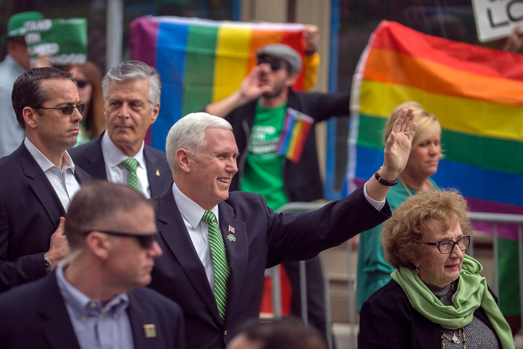 ". Vice President Mike Pence and his mother Nancy Pence Fritsch, right, wave while walking in the St. Patrick\'s Day parade Saturday, March 17, 2018, in Savannah, Ga.  Crowds behind barricades across the street cheered and chanted ""U-S-A\"" as Pence waved and gave a thumbs up sign. There were also a few protesters who followed Pence throughout the parade. (AP Photo/Stephen B. Morton)"