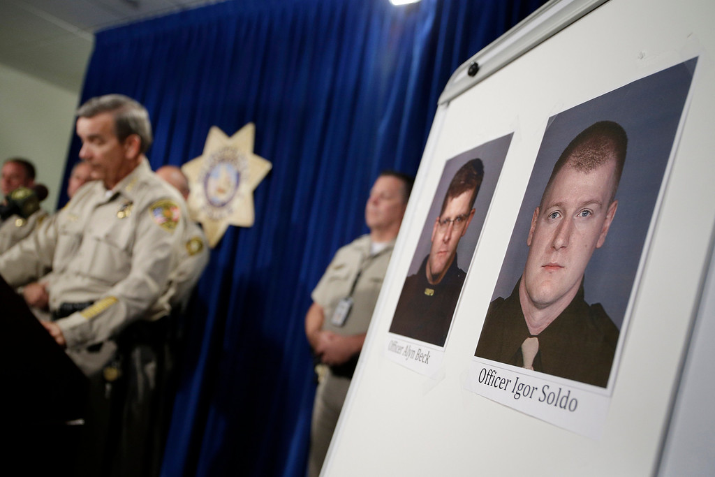 . Sheriff Doug Gillespie, left, speaks at a news conference on the shooting of two Las Vegas Metropolitan Police Department officers Sunday, June 8, 2014 in Las Vegas. The two officer killed were Alyn Beck and Igor Soldo. (AP Photo/John Locher)