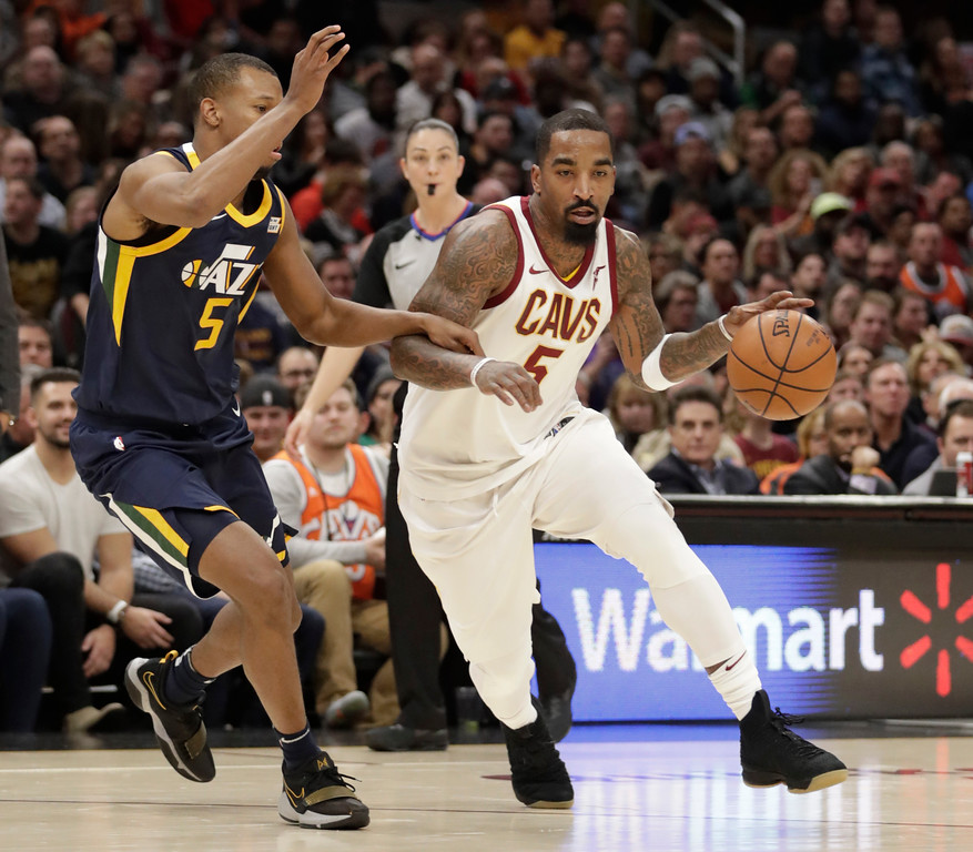 . Cleveland Cavaliers\' JR Smith, right, drive abasing Utah Jazz\'s Rodney Hood in the second half of an NBA basketball game, Saturday, Dec. 16, 2017, in Cleveland. (AP Photo/Tony Dejak)