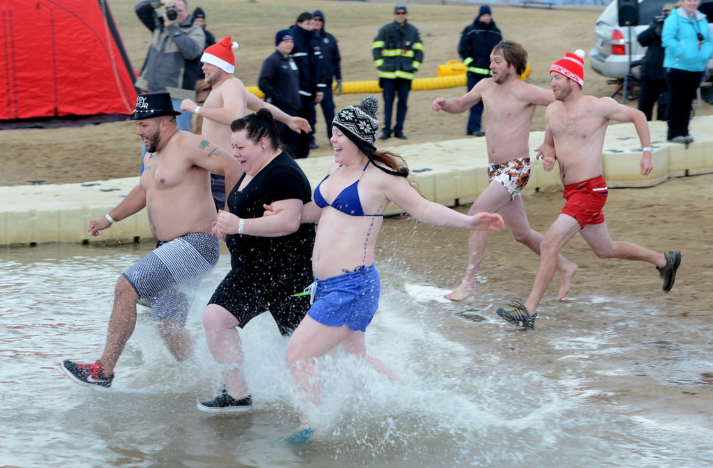 . Kyle Garrity, left , Kelly White, and Alyssa White, lead a wave into the icy water on Wednesday. The 31st annual Boulder Polar Plunge, at the Boulder Reservoir on New Year�s Day, to help the Boulder County AIDS Project and connectBCAP.  Cliff Grassmick/Daily Camera