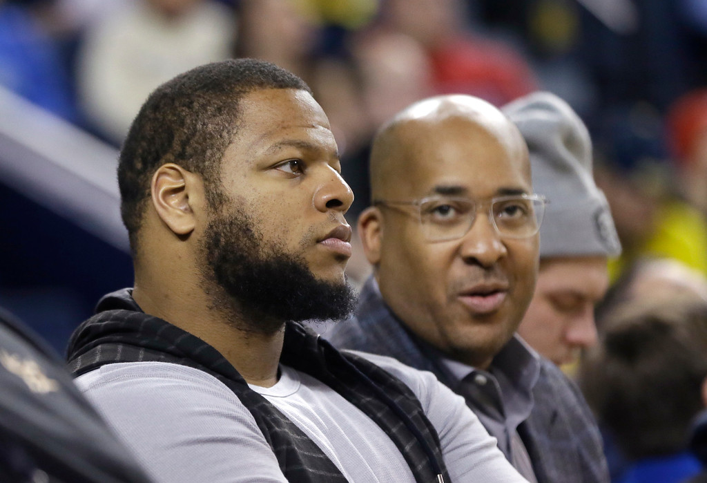 """. Detroit Lions defensive tackle Ndamukong Suh, left, watches an NCAA college basketball game between Michigan and Ohio State with consultant William Sydney \""""Wes\"""" Wesley, Sunday, Feb. 22, 2015, in Ann Arbor, Mich. Michigan defeated Ohio State 64-57. (AP Photo/Carlos Osorio)"""