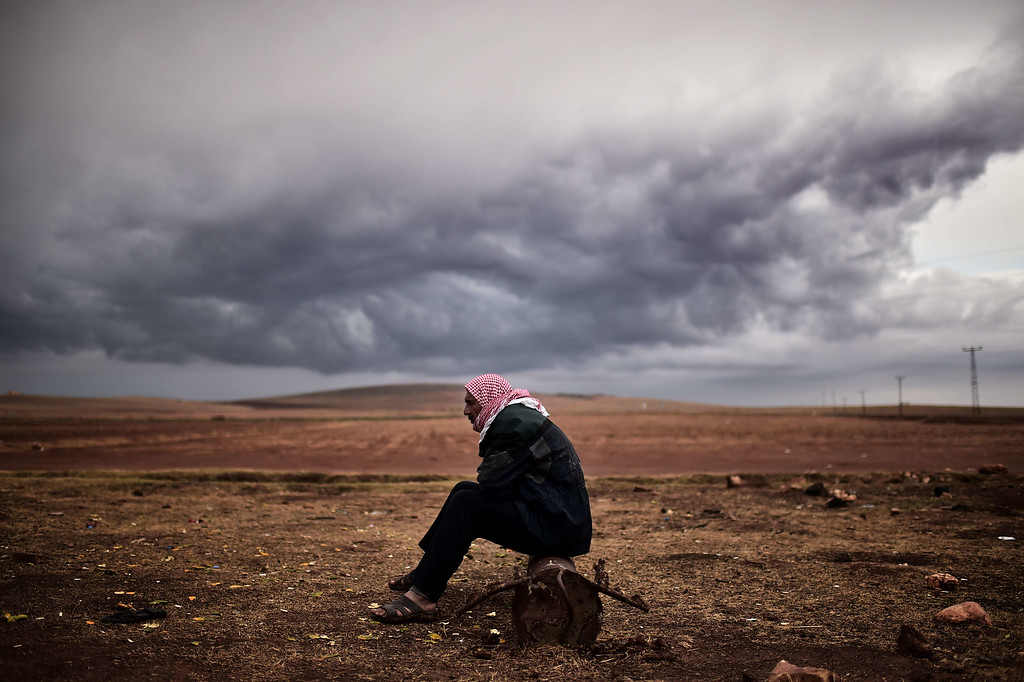 . A Kurdish man sits at the border area close to the southeastern village of Mursitpinar, in the Sanliurfa province, opposite the Syrian town of Kobane, also known as Ain al-Arab, where heavy fighting between Islamic State militants and Kurdish fighters is taking place, on October 16, 2014. Turkey\'s ruling party said it was optimistic about the prospects for the peace process with Kurdish rebels after a spate of violence raised concern about its viability.  AFP PHOTO / ARIS MESSINIS/AFP/Getty Images
