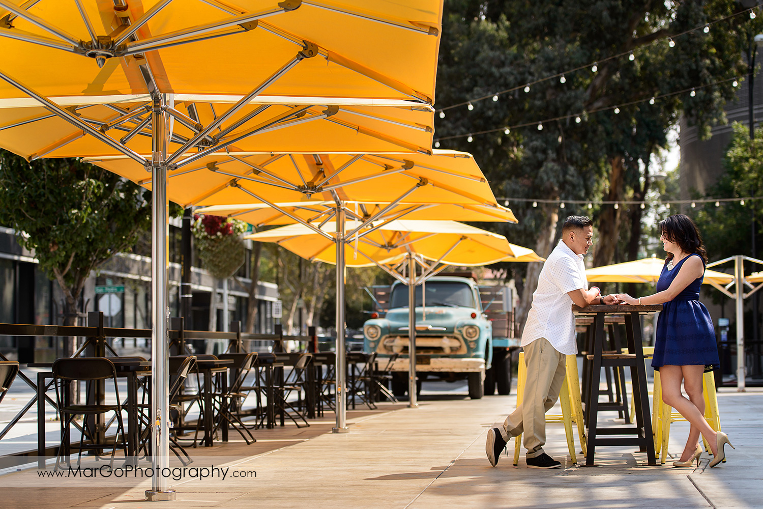 woman in blue dress and man in white shirt standing at black table under yellow umbrella and talking during engagement session at San Pedro Square Market in San Jose