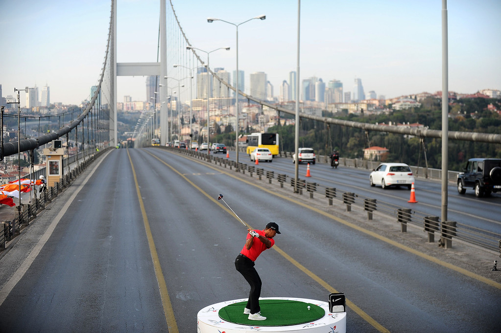 . U.S. golfer Tiger Woods hits a ball as he poses during an event to promote the upcoming Turkish Airlines Open golf tournament, on the Bosphorus Bridge that links the city\'s European and Asian sides, in Istanbul, on November 5, 2013. Woods was in Turkey to attend the tournament, which took place between November 7 to 10.  BULENT KILIC/AFP/Getty Images