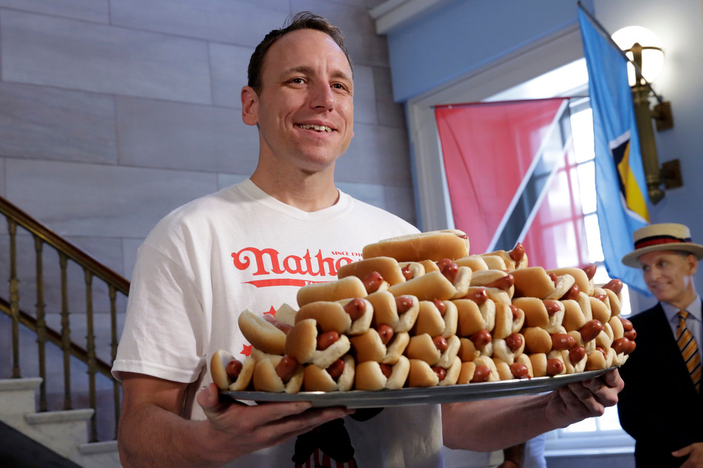. Current men\'s champion Joey Chestnut, of San Jose, CA., holds a tray of hot dogs during the weigh-in for the 2017 Nathan\'s Hot Dog Eating Contest, in Brooklyn Borough Hall, in New York, Monday, July 3, 2017. Chestnut weighed-in at 221.5 pounds. (AP Photo/Richard Drew)