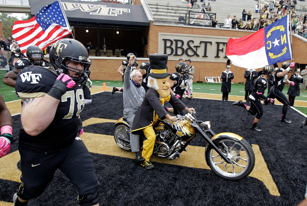 . Arnold Palmer, center, waves to the crowd as he rides on the back of a motorcycle as Wake Forest players take the field before an NCAA college football game against Maryland in Winston-Salem, N.C., Saturday, Oct. 19, 2013. Palmer played golf at Wake Forest and the school dedicated a statue to him last week. (AP Photo/Chuck Burton)