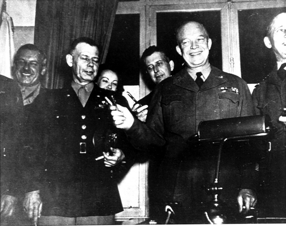 . General Dwight D. Eisenhower holds up a V-for-Victory gesture with the two pens used by high ranking German officers in signing the surrender document at the school house in Reims, France on May 7, 1945.  Kay Summersby, background left, Eisenhower\'s chauffeur-secretary, is seen peeking over General Walter Bedell Smith\'s shoulder.  Her face was censored from the official photo taken by T/Sgt. Al Meserlin, Ike\'s personal photographer.  Other officers are not identified.  (AP Photo/Al Meserlin)