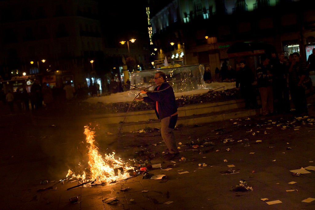 . A protester burns trash during a demonstration against layoffs of street cleaners and garbage collectors in Madrid, Spain, Monday, Nov. 4, 2013. Trash collectors in Madrid have started bonfires and set off firecrackers during a noisy protest in one of the Spanish capitalís main squares as they prepare to start an open-ended strike. Hundreds of street cleaners and garbage collectors who work in the cityís public parks converged on the Puerta del Sol plaza late Monday. (AP Photo/Daniel Ochoa de Olza)
