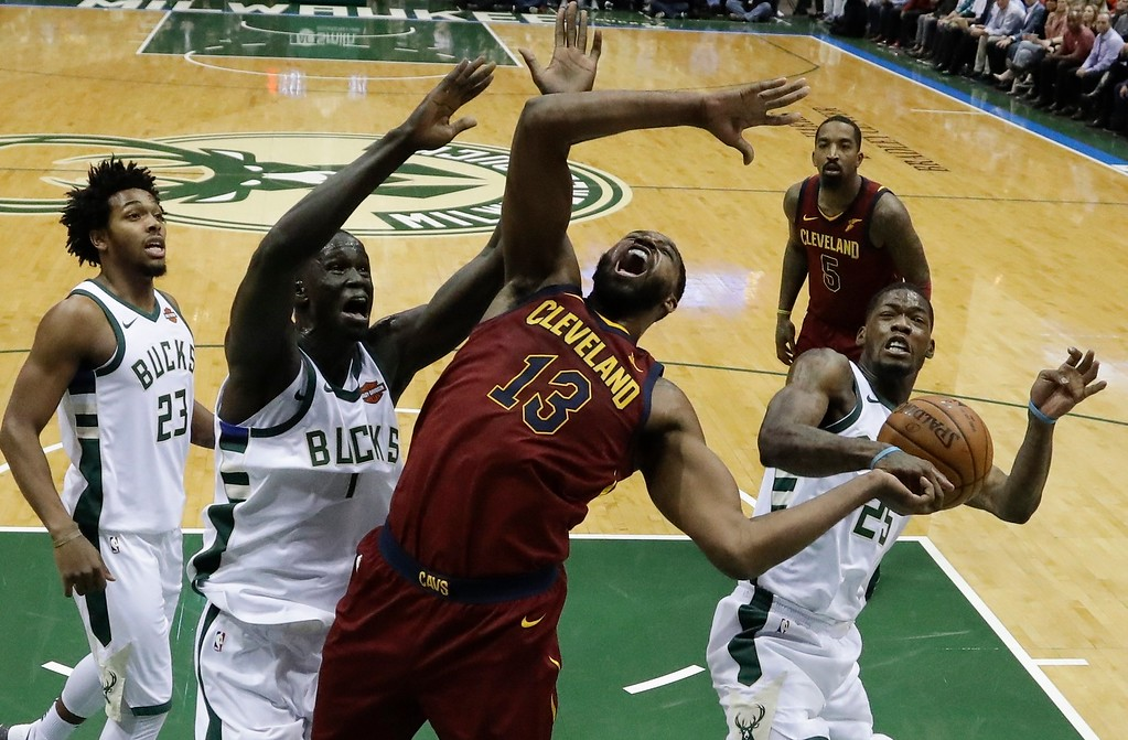 . Cleveland Cavaliers\' Tristan Thompson is fouled as he drives between Milwaukee Bucks\' Thon Maker (7) and DeAndre Liggins (25)nduring the first half of an NBA basketball game Tuesday, Dec. 19, 2017, in Milwaukee. (AP Photo/Morry Gash)