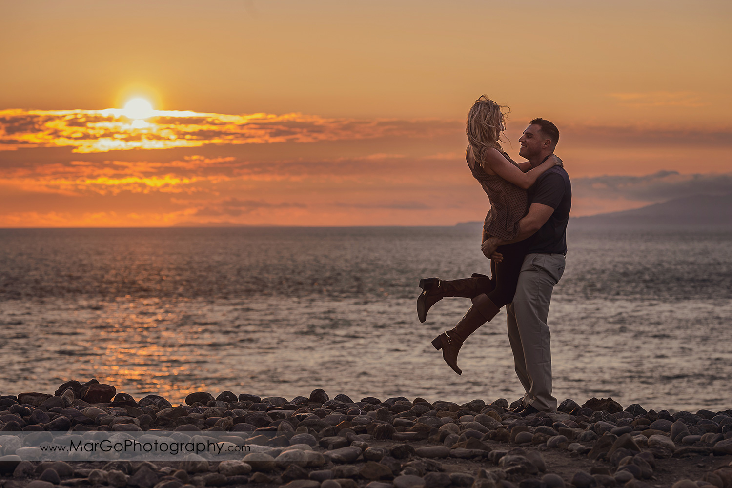 man in navy blue shirt lifting woman in brown tunic in the stone labyrinth during sunset engagement session at San Francisco Lands End