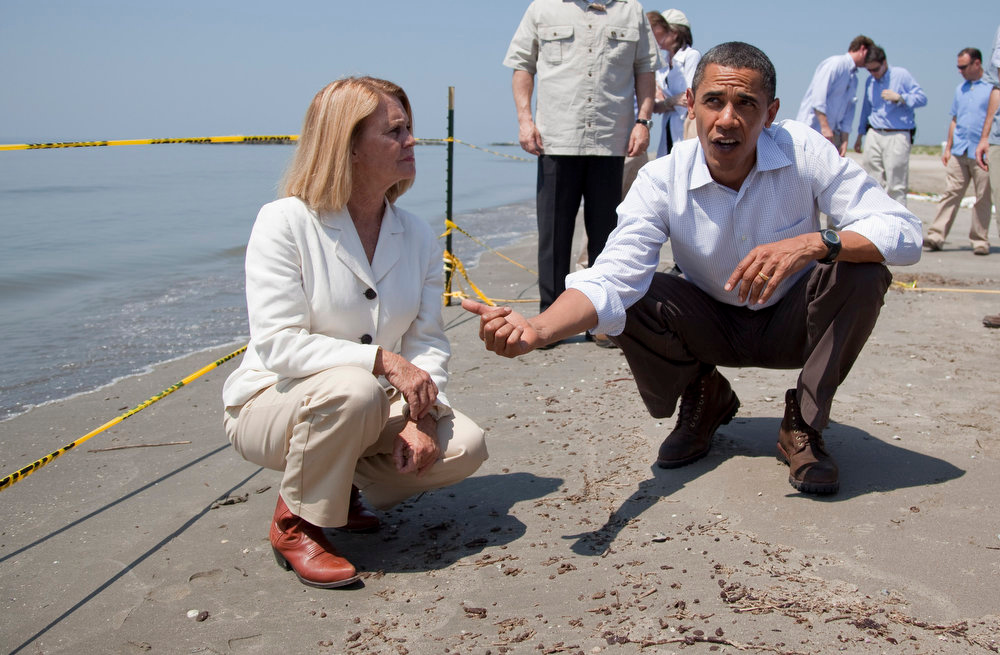 ". President Barack Obama and LaFourche Parish President Charlotte Randolph look at oil washed up as ""tar balls\"" in Port Fourchon, La., during a tour of areas affected by the Gulf Coast oil spill in this May 28, 2010 file photo. A high-stakes trial to assign blame and help figure out exactly how much more BP and other companies should pay for the spill began Monday, Feb. 25, 2013. (AP Photo/Evan Vucci, File)"