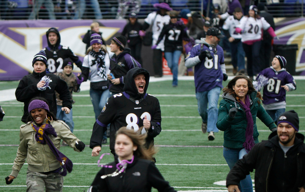 . Fans of Super Bowl XLVII champion Baltimore Ravens run onto their home stadium\'s playing field before a rally in Baltimore February 5, 2013. The Ravens defeated the San Francisco 49ers to win the NFL championship.     REUTERS/Gary Cameron