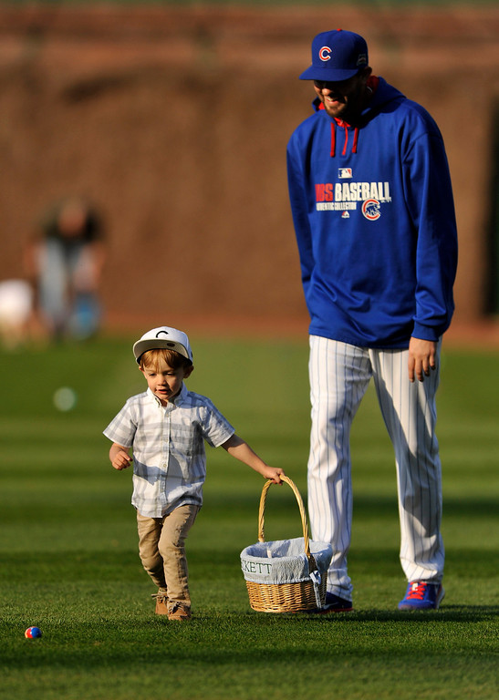 . Chicago Cubs pitcher Jason Hammell and son Beckett, 2, hunt for Easter eggs at Wrigley Field after a baseball game between the Cubs and the Cincinnati Reds in Chicago, Sunday, April 20, 2014. (AP Photo/Paul Beaty)
