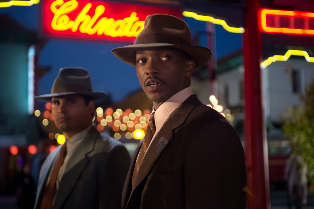 """. This film image released by Warner Bros. Pictures shows Michael Pena, left, as Officer Navidad Ramirez and Anthony Mackie, as Officer Coleman Harris, in \""""Gangster Squad.\"""" (AP Photo/Warner Bros. Pictures, Jamie Trueblood)"""