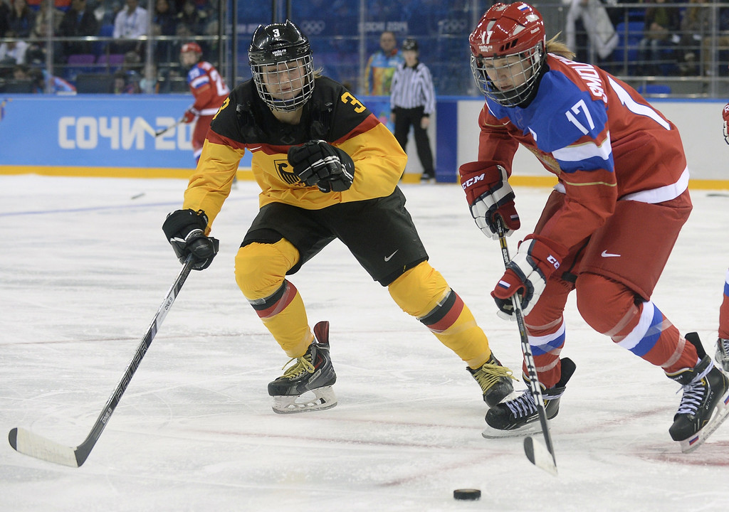 . Russia\'s Yekaterina Smolentseva (R) vies with Germany\'s Sophie Kratzer during a Women\'s Ice Hockey Group B match between Russia and Germany at the Shayba Arena during the Sochi Winter Olympics on February 9, 2014.  ALEXANDER NEMENOV/AFP/Getty Images