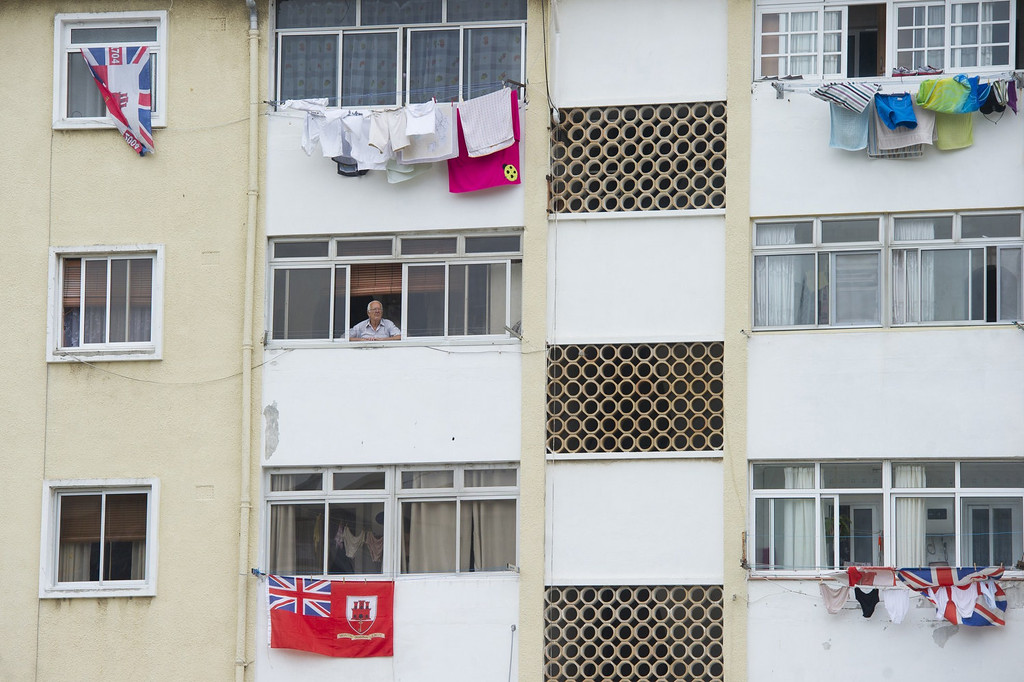 """. A man stands at a window above British flags in Gibraltar on August 13, 2013 as Spain enforced tight border checks in a growing row with Britain over the tiny territory and its surrounding waters. On the \""""Rock\"""" itself, defiant residents declared themselves thoroughly British, surrounded by English pubs serving fish and chips, Royal Mail letter boxes, bright red telephone cabins and the occasional monkey.   MARCOS MORENO/AFP/Getty Images"""