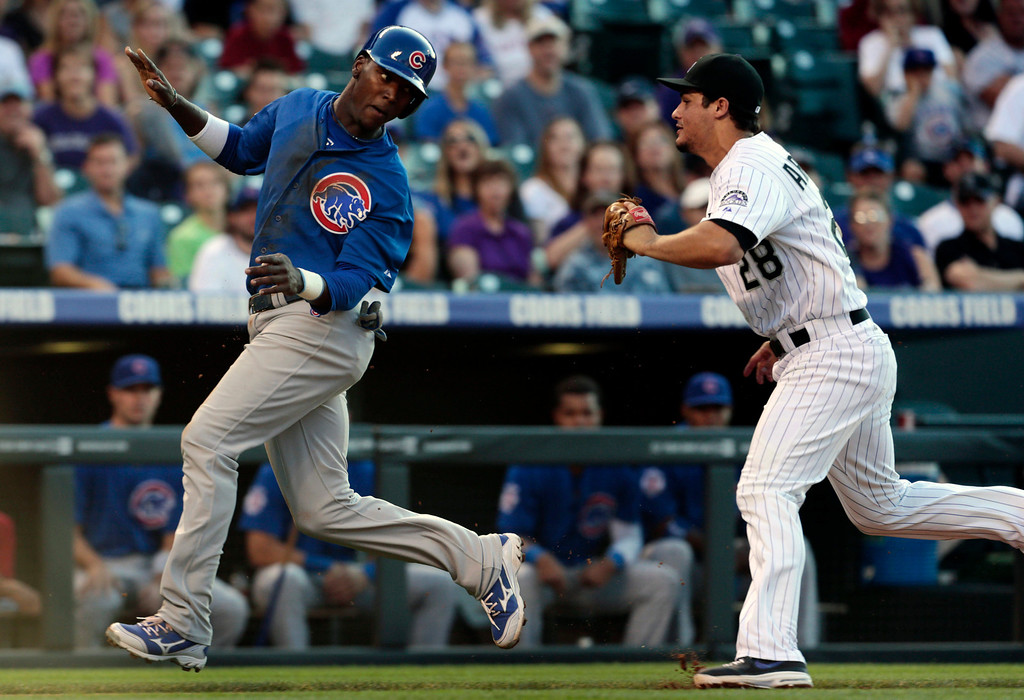 . Chicago Cubs\' Junior Lake, left, runs from Colorado Rockies third baseman Nolan Arenado before being tagged out during a rundown between third base and home plate in the second inning of a baseball game in Denver, Friday, July 19, 2013. (AP Photo/Joe Mahoney)