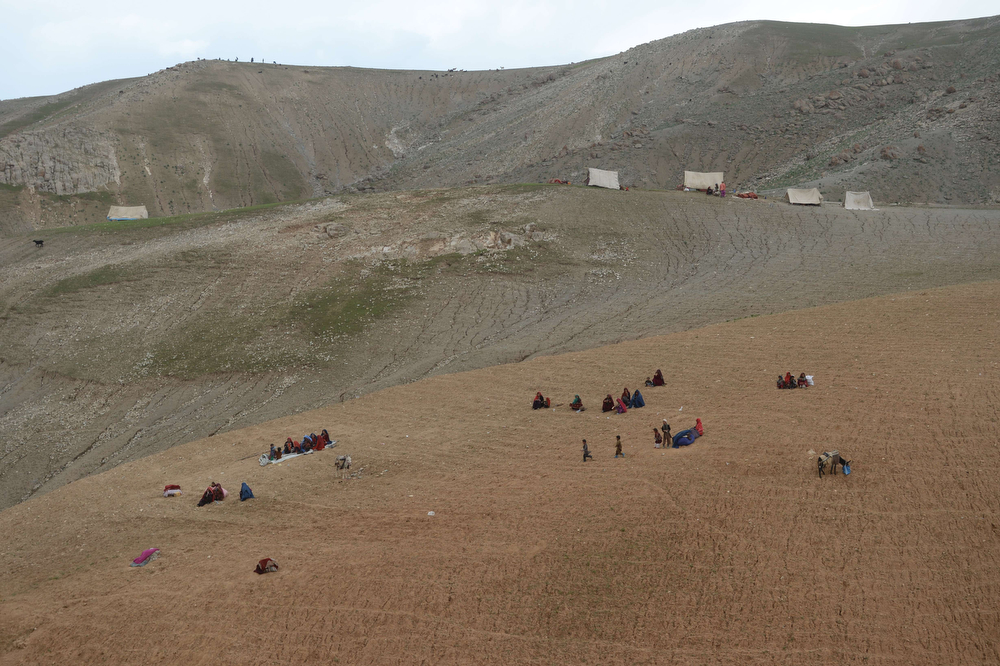 . Afghan villagers look on at the scene in Argo district of Badakhshan province on May 3, 2014 after a massive landslide May 2 buried a village. Rescuers searched in vain for survivors May 3 after a landslide buried an Afghan village, killing 350 people and leaving thousands of others feared dead amid warnings that more earth could sweep down the hillside. Local people made desperate efforts to find victims trapped under a massive river of mud that engulfed Aab Bareek village in Badakhshan province, where little sign remained of hundreds of destroyed homes. (SHAH MARAI/AFP/Getty Images)
