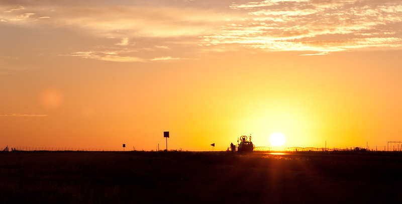 A racer from another team  rides into the sunrise in New Mexico.