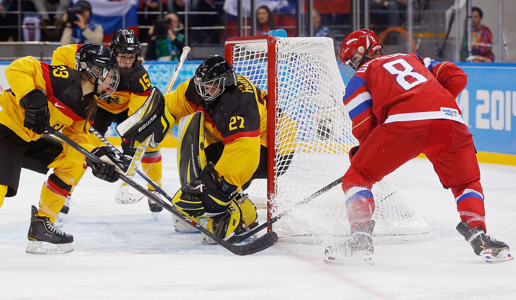 . Iya Govrilova of Russia scores a goal past Goalkeeper Viona Harrer and Tanja Eisenschmid,left, of Germany during the third period of the 2014 Winter Olympics women\'s ice hockey game at Shayba Arena, Sunday, Feb. 9, 2014, in Sochi, Russia. (AP Photo/Petr David Josek)