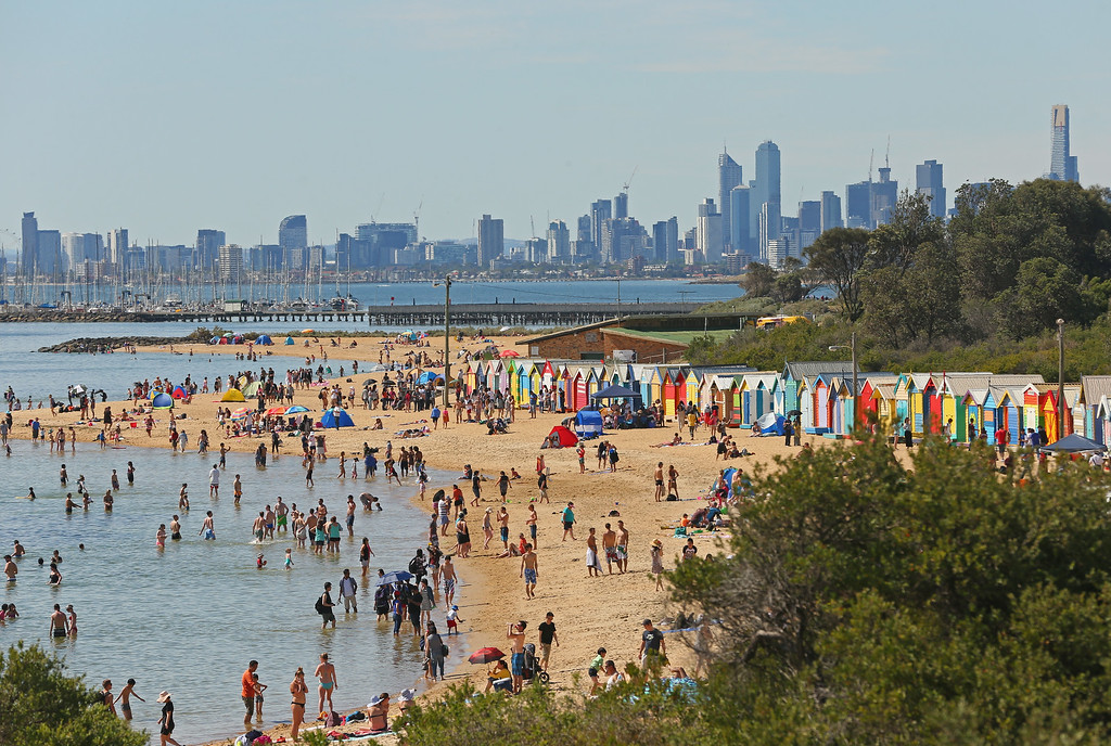 . MELBOURNE, AUSTRALIA - DECEMBER 25:  People enjoy a day at the beach on Christmas Day at Brighton Beach on December 25, 2013 in Melbourne, Australia.  Brighton Beach features 82 colourful bathing boxes, which are one of the tourist icons of Melbourne. Temperatures in Melbourne on Christmas Day topped thirty degrees celcius.  (Photo by Scott Barbour/Getty Images)