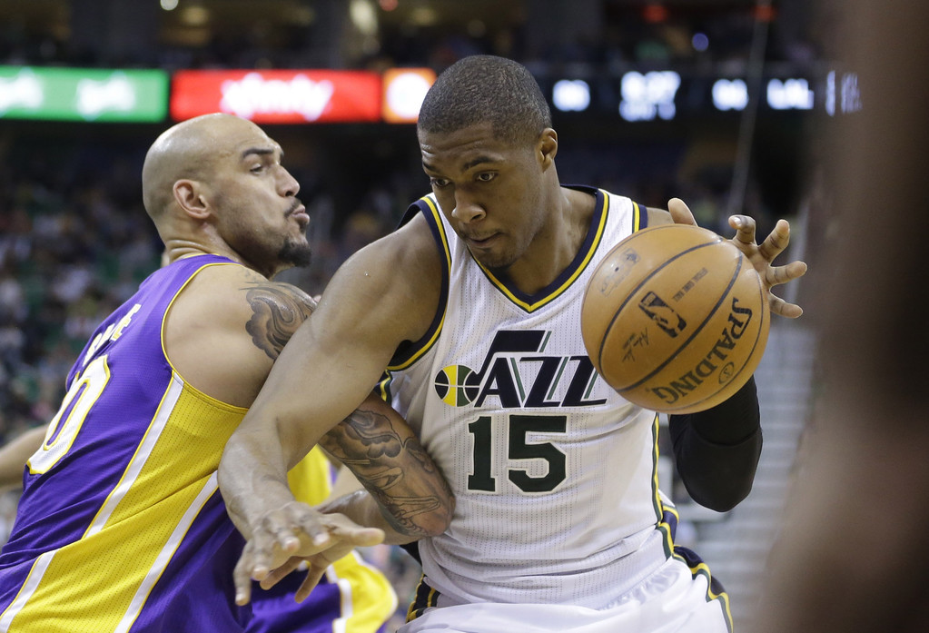 . Los Angeles Lakers\' Robert Sacre, left, defends against Utah Jazz\'s Derrick Favors (15) in the second half during an NBA basketball game Monday, April 14, 2014, in Salt Lake City, Utah. (AP Photo/Rick Bowmer)