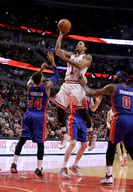 . Chicago Bulls guard Derrick Rose (1) shoots over Detroit Pistons guard D.J. Augustin (14) and Andre Drummond during the second half of an NBA basketball game Monday, Nov. 10, 2014, in Chicago. The Bulls won 102-91. (AP Photo/Charles Rex Arbogast)