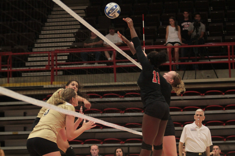 Number 1, Heather Feldman, and number 11, Tyler Cockrell, prepare to block a spike.