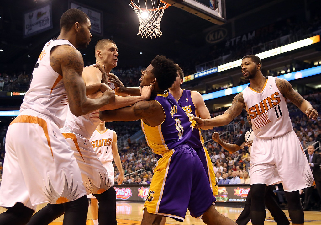 . Nick Young #0 of the Los Angeles Lakers pushes Alex Len #21 of the Phoenix Suns after a flagrant foul as Marcus Morris #15 (L) and Markieff Morris #11 (R) look on during the first half of the NBA game at US Airways Center on January 15, 2014 in Phoenix, Arizona.    (Photo by Christian Petersen/Getty Images)
