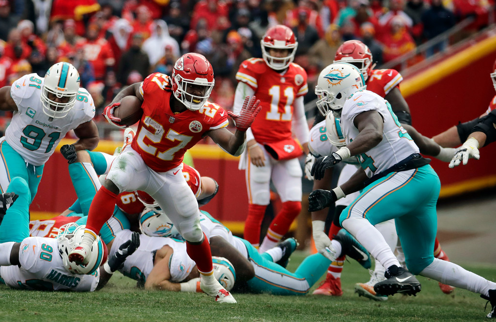 . Kansas City Chiefs running back Kareem Hunt (27) carries the ball away from Miami Dolphins defenders during the first half of an NFL football game in Kansas City, Mo., Sunday, Dec. 24, 2017. (AP Photo/Charlie Riedel)