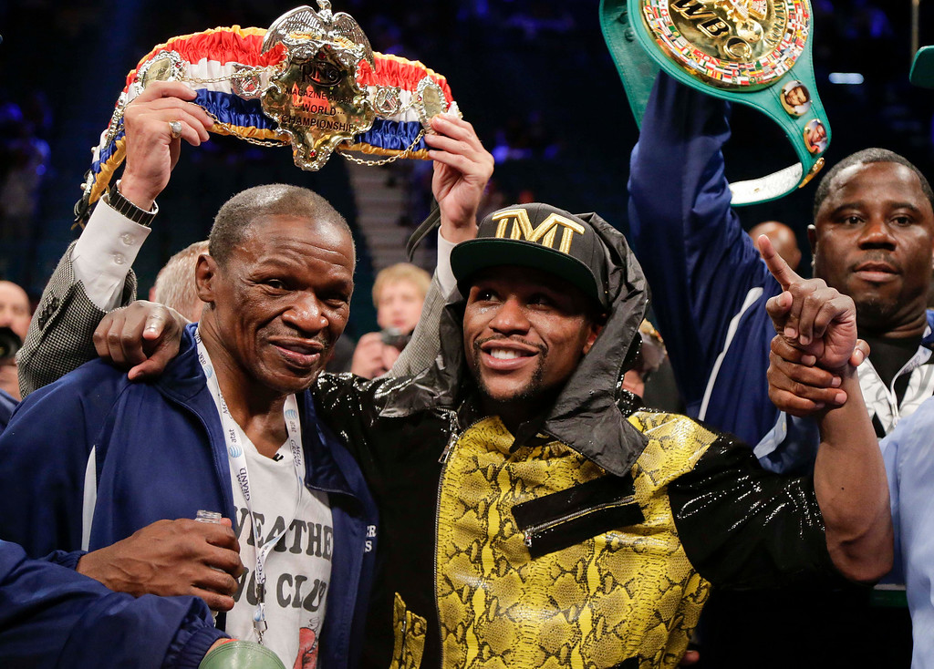 . Floyd Mayweather Jr., right, poses for photos with his father, Floyd Mayeather Sr. after defeating Robert Guerrero by unanimous decision in a WBC welterweight title fight, Saturday, May 4, 2013, in Las Vegas. (AP Photo/Rick Bowmer)