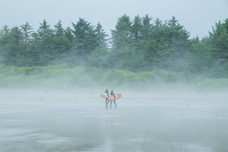 Surfers emerging from the fog