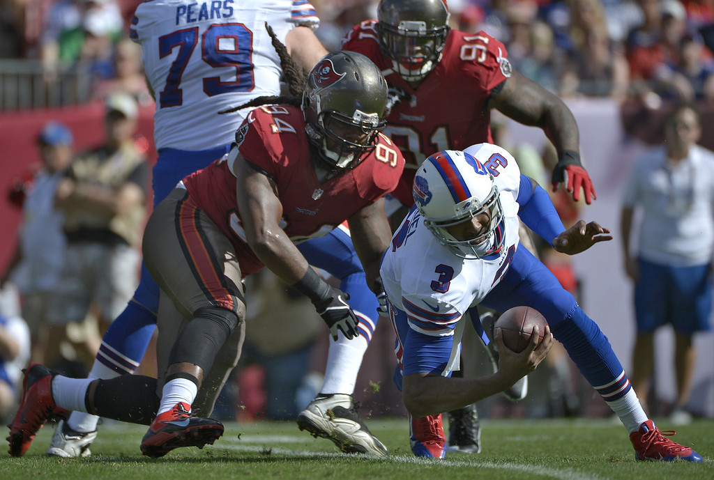 . Buffalo Bills quarterback EJ Manuel (3) eludes Tampa Bay Buccaneers defensive end Adrian Clayborn (94) on a run during the first quarter of an NFL football game on Sunday, Dec. 8, 2013, in Tampa, Fla. (AP Photo/Phelan M. Ebenhack)