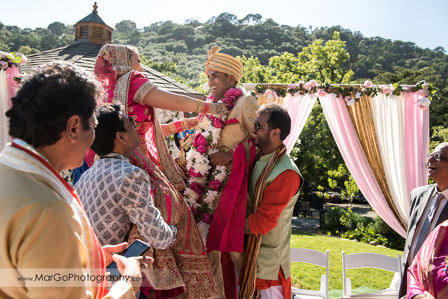 bride and groom exchanging the fresh flower garlands during Indian wedding ceremony at Elliston Vineyards in Sunol