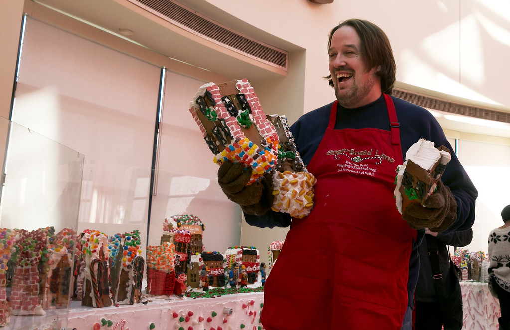 . Chef Jon Lovitch carries some of his gingerbread house creations for the GingerBread Lane display, at the New York Hall of Science, in the Queens borough of New York, Thursday, Nov. 13, 2014. Lovitch, a Manhattan chef who holds the Guinness record for creating the world\'s largest collection of gingerbread houses, is now going for another record, competing against himself by assembling more than 1,000 new ones. (AP Photo/Richard Drew)