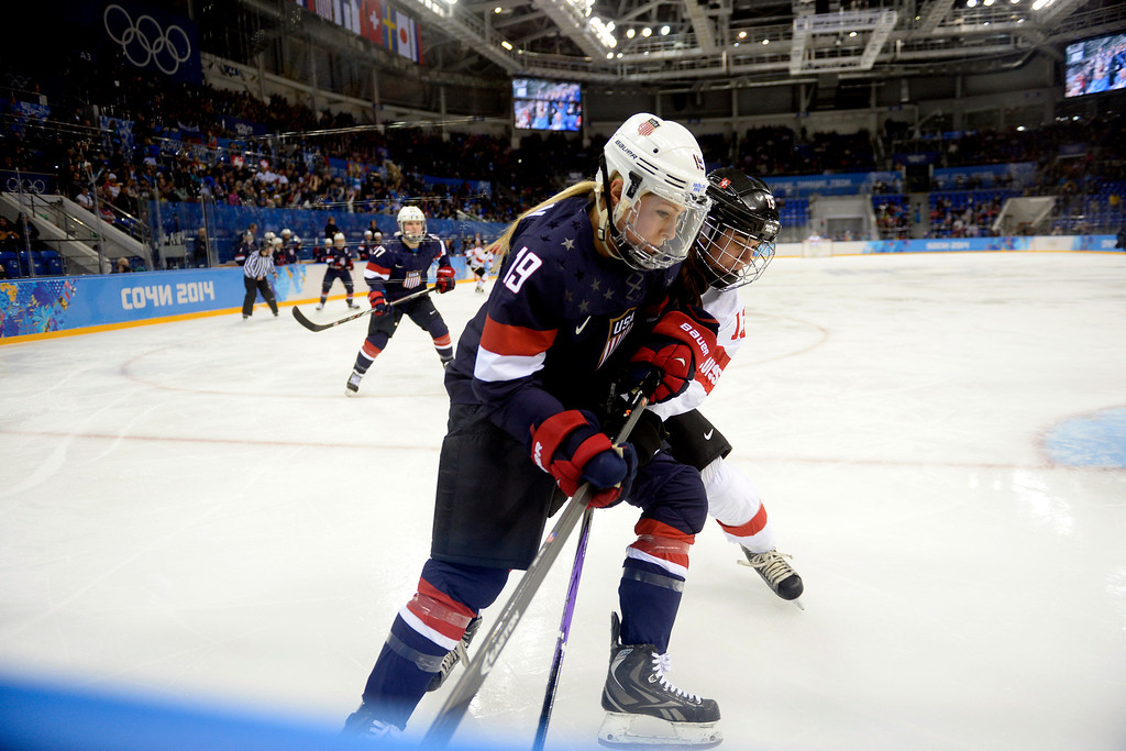 . Gigi Marvin (19) of the U.S.A. and Sara Benz (13) of the Switzerland battle for position near the boards during the first period of action at the Shayba Arena. Sochi 2014 Winter Olympics on Monday, February 10, 2014. (Photo by AAron Ontiveroz/The Denver Post)