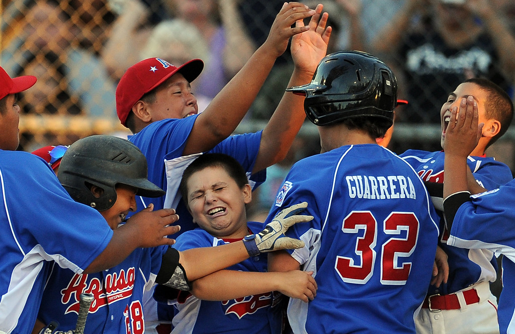 . Azusa\'s Anthony Guarrera (32) mobbed by teammates after hitting a solo home run against  La Verne in the fourth inning of a championship Little League Section 3 championship baseball game at Homer Briggs Park on Wednesday, July 17, 2013 in Ontario, Calif. La Verne won 3-2 in 8 innings. 