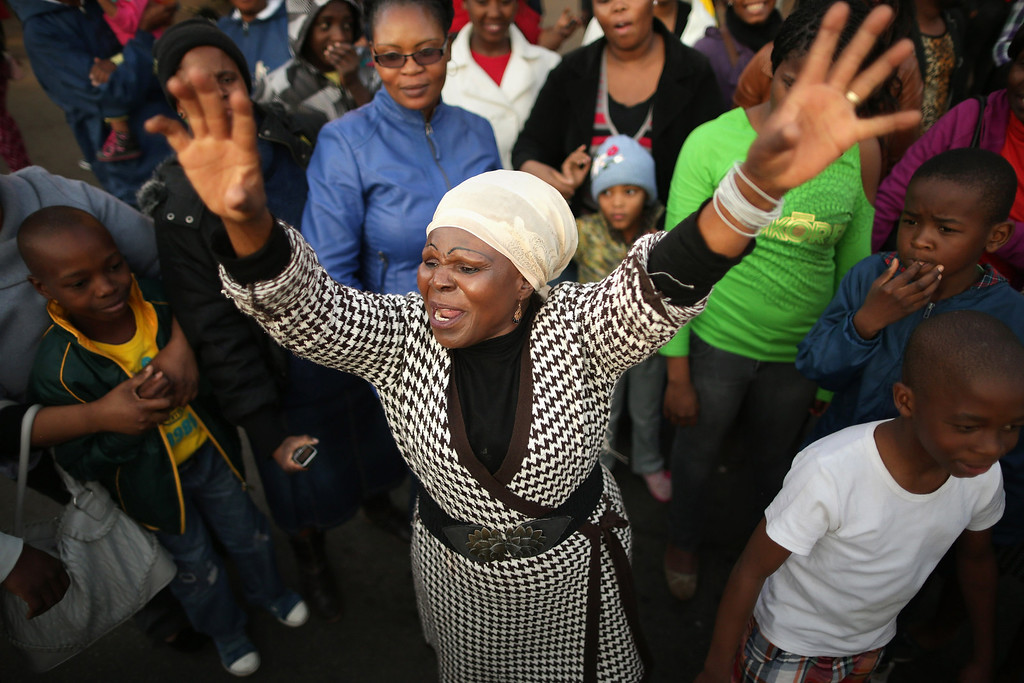 """. PRETORIA, SOUTH AFRICA - JUNE 25:  Florence Nyadzani (C), 58, leads people in songs and cheers of support outside of the Mediclinic Heart Hospital where former South African President Nelson Mandela is being treated June 25, 2013 in Pretoria, South Africa. \""""I got my freedom because of Mandela,\"""" Nyadzani said. \""""We pray every day because we love him.\"""" South African President Jacob Zuma confirmed on June 23 that Mandela\'s condition has become critical since he was admitted to the hospital over two weeks ago for a recurring lung infection.  (Photo by Chip Somodevilla/Getty Images)"""