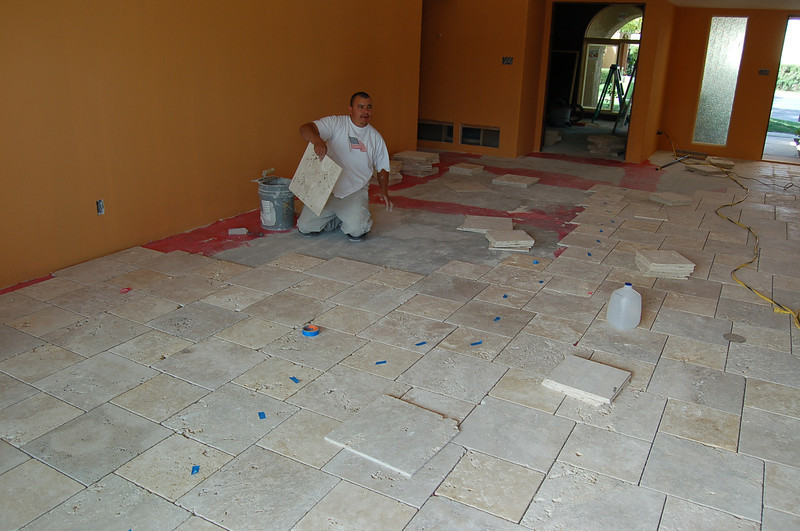 Hard at work laying travertine tile in the living room.