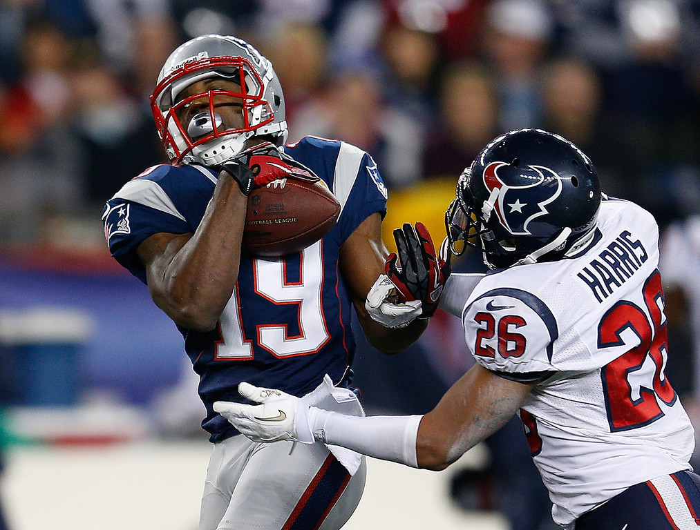 . FOXBORO, MA - DECEMBER 10:  Donte\' Stallworth #19 of the New England Patriots catches a pass despite the defense of Brandon Harris #26 of the Houston Texans and runs the ball into the end zone for a touchdown in the second half at Gillette Stadium on December 10, 2012 in Foxboro, Massachusetts. (Photo by Jim Rogash/Getty Images)