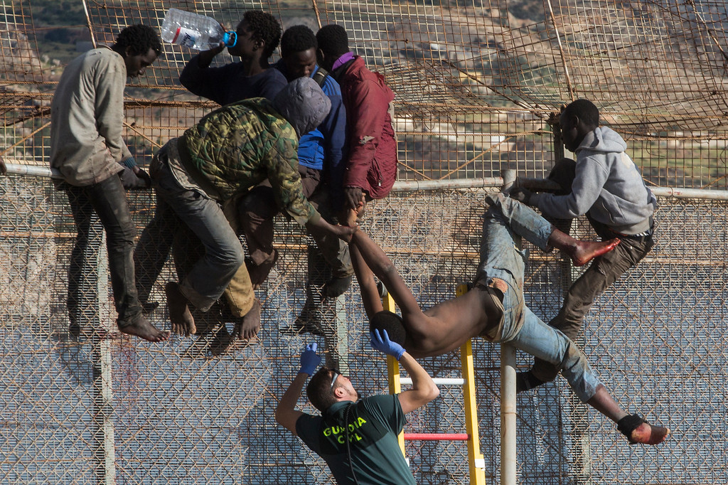 . A sub-Saharan migrant is helped by a Spanish Guardia Civil officer after he fainted on top of a metallic fence that divides Morocco and the Spanish enclave of Melilla, Thursday, April 3, 2014. Spanish and Moroccan police have thwarted a fresh attempt by dozens of African migrants to try to scale border fences to enter the Spanish enclave of Melilla. Thousands of sub-Saharan migrants seeking a better life in Europe are living illegally in Morocco and regularly try to enter Melilla in the hope of later making it to mainland Spain. (AP Photo/Santi Palacios, File)