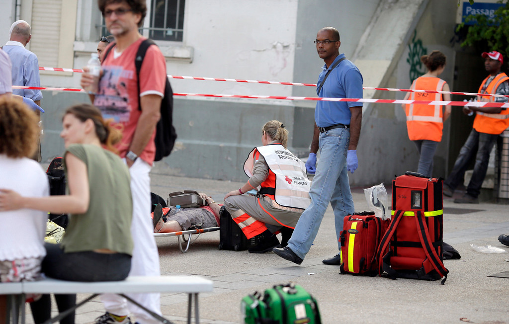 . A Red Cross worker attends to a person on a stretcher at the site of a train accident in the railway station of Bretigny-sur-Orge, Friday, July 12, 2013 near Paris. (AP Photo/Kenzo Tribouillard, Pool)
