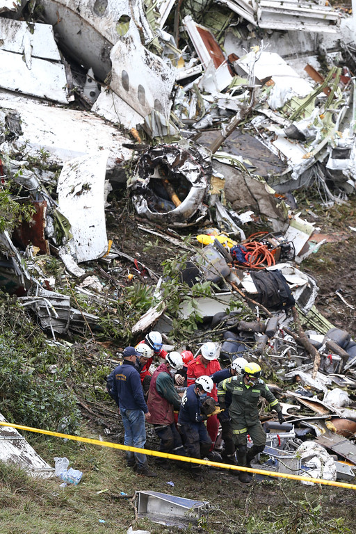 . Rescue workers recover a body from the wreckage site of an airplane crash, in La Union, a mountainous area near Medellin, Colombia, Tuesday , Nov. 29, 2016. The chartered plane was carrying a Brazilian soccer team to the biggest match of its history when it crashed into a Colombian hillside and broke into pieces, Colombian officials said Tuesday. (AP Photo/Fernando Vergara)