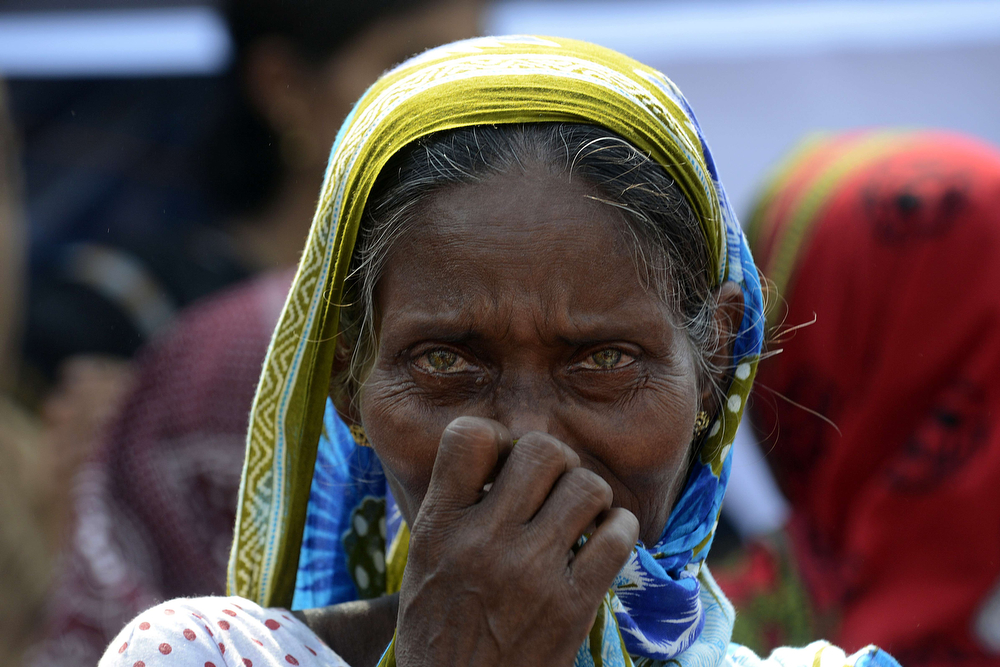 . A Bangladeshi mourner and relative of a victim of the Rana Plaza building collapse reacts as she takes part in a protest marking the first anniversary of the disaster at the site where the building once stood in Savar on the outskirts of Dhaka on April 24, 2014. The Rana Plaza building collapsed on April 24, 2013, killing 1138 workers in the world\'s worst garment factory disaster. Western fashion brands faced pressure to increase help for victims as mass protests marked the anniversary. Thousands of people, some wearing funeral shrouds, staged demonstrations at the site of the now-infamous Rana Plaza factory complex. (MUNIR UZ ZAMAN/AFP/Getty Images)