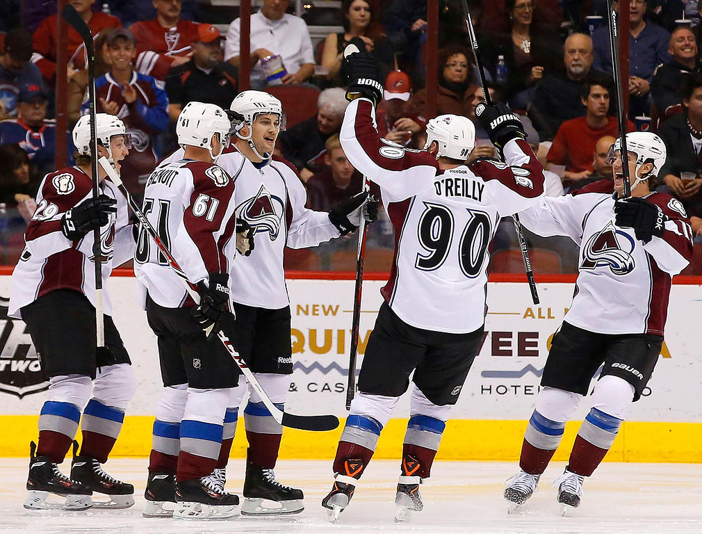 . Colorado Avalanche\'s John Mitchell, center, celebrates his goal against the Phoenix Coyotes with teammates Nathan MacKinnon (29), Andre Benoit (61), P.A. Parenteau, right, during the second period of an NHL hockey game Thursday, Nov. 21, 2013, in Glendale, Ariz. (AP Photo/Ross D. Franklin)