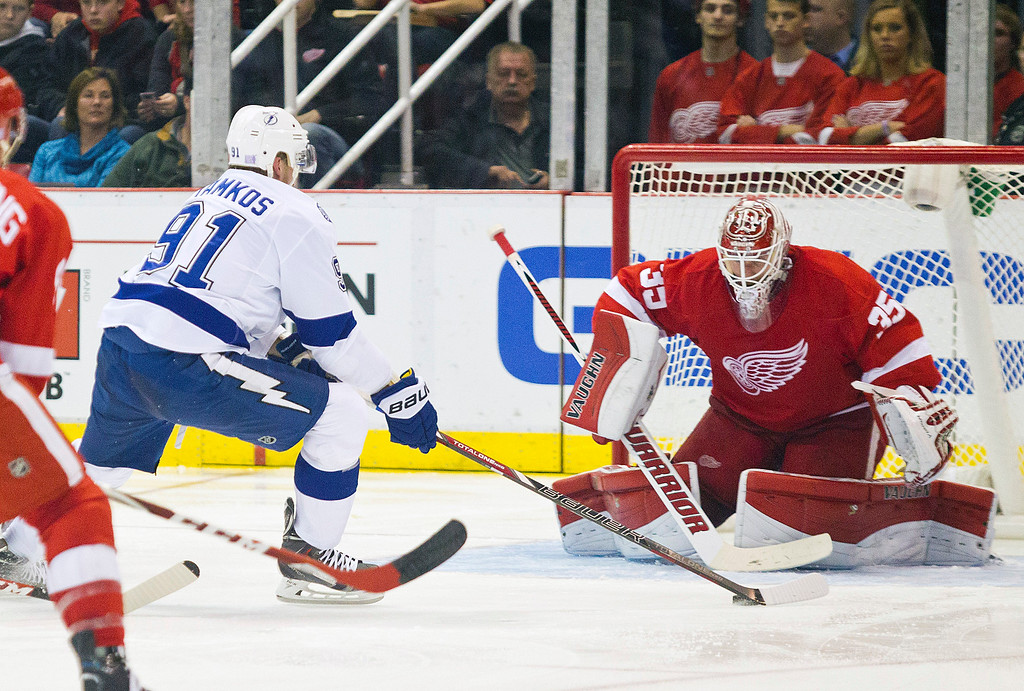 . Tampa Bay Lightning forward Steven Stamkos (91) charges with the puck at Detroit Red Wings goalie Jimmy Howard (35) during the second period of an NHL hockey game in Detroit, Mich., Sunday, Nov. 9, 2014. (AP Photo/Tony Ding)