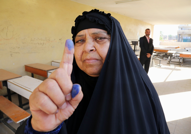 Description of . An elderly Iraqi woman shows her ink-stained finger after casting her vote inside a polling station for parliamentary elections in Baghdad, Iraq, Wednesday, April 30, 2014. Iraq is holding its third parliamentary elections since the U.S.-led invasion that toppled dictator Saddam Hussein. More than 22 million voters are eligible to cast their ballots to choose 328 lawmakers out of more than 9,000 candidates. (AP Photo/Karim Kadim)