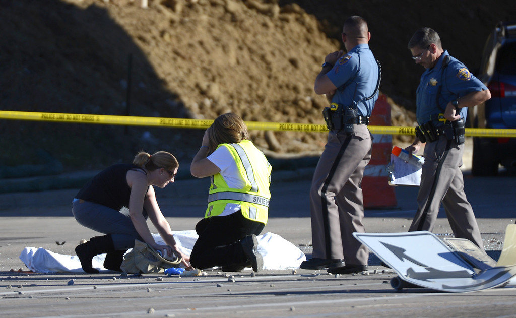 . Family is escorted to a victim at the fatal crash at Broadwway at the C-470 exit in the northbound lane of Broadway.  John Leyba, The Denver Post